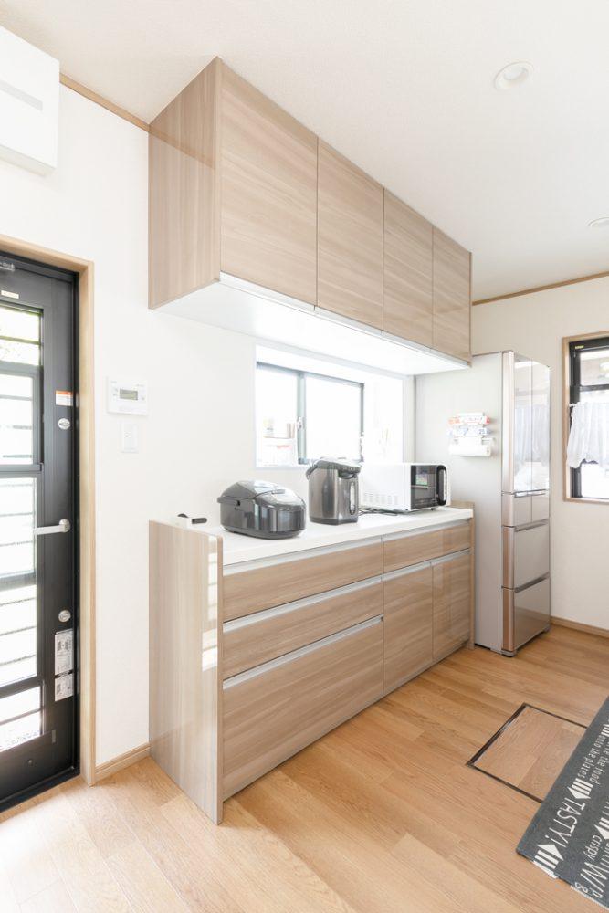 キッチン 施工後<br /> 元々キッチンが設置されていた壁にはカップボードを設置し、収納力たっぷりの空間に。