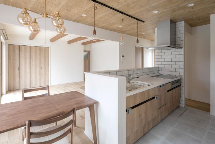 娘さん夫婦が暮らす1Fには、広々としたリビング空間を実現。対面式のキッチンがつながりを与え、天井の梁とウッディなクロスが自然の雰囲気を演出します。