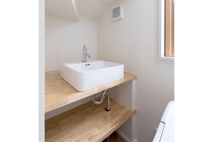 階段下のスペースを有効活用したラバトリーは手洗いと収納スペースを広々確保。ゆとりある空間に仕上がりました。